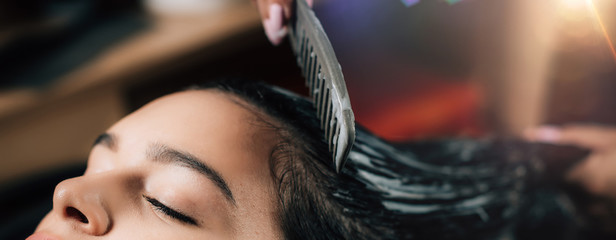 Hairdresser Treating Woman's Hair with Revitalizing Hair Pack