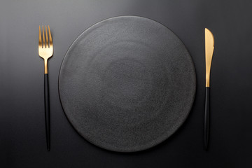 Empty black plate with fork and knife on black background. Top view.