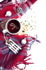Hot christmas beverage black tea with thyme in mug with new year decorations, Cone, present, silver ball, plaid on white. Winter time top view