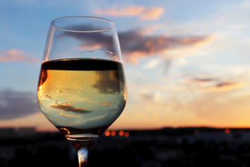 Glass of white wine on colorful sunset background, sun and sky are reflected in alcohol drink. Concept of celebration, evening party at resort, romantic dinner outdoors