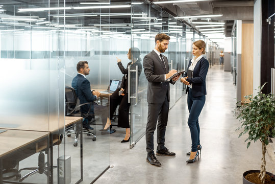 Business people talking in the hallway of the modern office building with employees working behind glass partitions. Work in a large business corporation