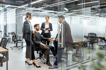 Group of strictly dressed business people having a discussion, sitting at the workplace with a computer in the modern office with glass partitions