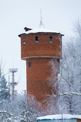 Brick water tower in the countryside in winter