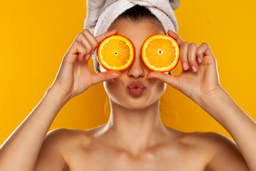 Young beautiful woman with towel on her head holding slices of orange in front of her eyes on yellow background Fototapete