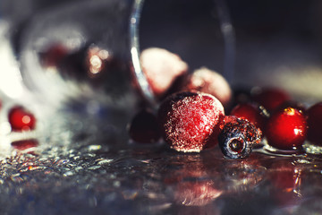 closeup frozen berries on the glass with reflection . frozen berries  on a dark background macro. cranberries blueberries and cherries