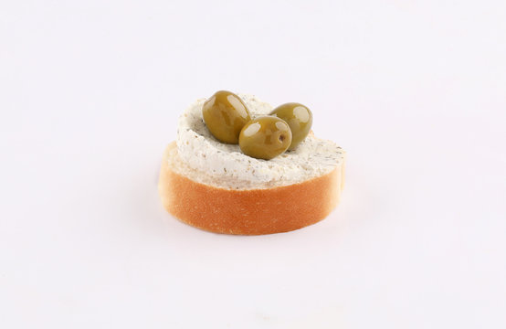 opened sandwich appetizer with spread cheese olives topping angle view