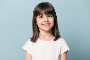 Close up portrait with smiling little brown-haired girl. Wall mural