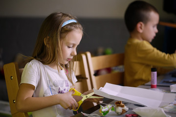 Children make up of paper at work table