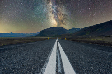 Milky way over mountains at the end of a long road. Scenery and night photography concept..........