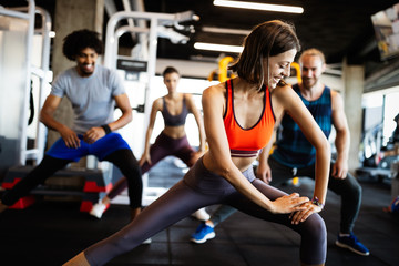 Attractive sports people are working out in gym