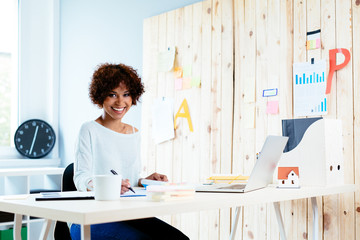 Young freelancer sitting in home office and smiling at camera