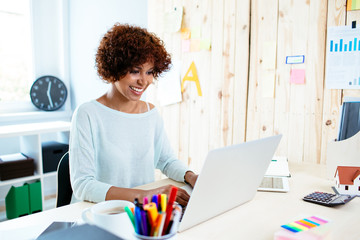 Happy young woman working freelance from home with laptop