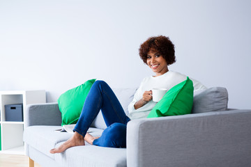 Smiling young woman looking at camera while sitting on sofa with coffee at home
