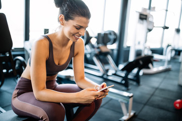 Portrait of sport woman using mobile after exercise at gym. Wall mural