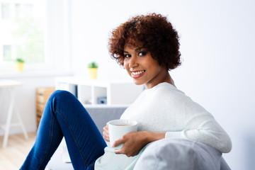 Portrait of cheerful young woman sitting on couch with coffee and looking at camera