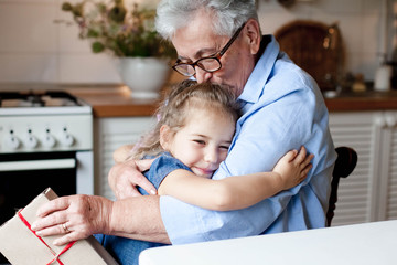 Grandmother congratulates child with gift box. Kid and senior woman are hugging in cozy home kitchen. Family enjoying kindness, tenderness. Lifestyle moment. Happy holidays Christmas, Birthday