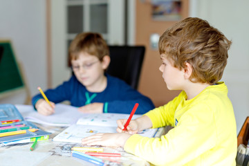 Two little kids boys at home making homework. Little concentrated children writing with colorful...