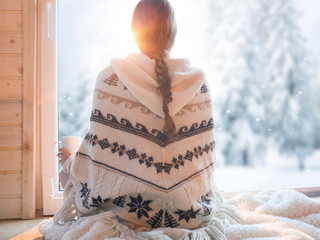 Woman wearing nordic style poncho sitting home by the window with cup of coffee, winter woods landscape outside