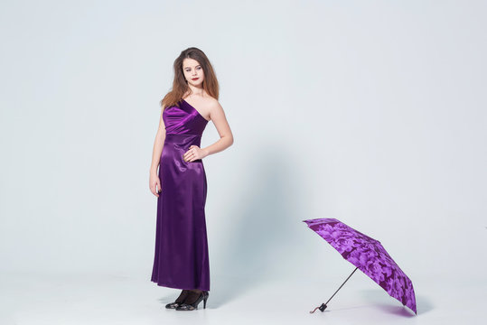 A girl in a purple dress on a white background with an umbrella in her hands. Girl and purple umbrella.  Young woman in evening dress on white background