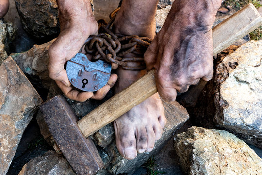 The dirty hands of a slave hold a hammer among the stones. Slave hard labor in the quarries. The symbol of slave labor.