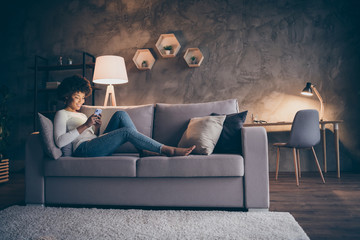 Profile photo of pretty dark skin curly lady domestic atmosphere texting telephone lying comfy couch in lamp light wear casual outfit evening living room indoors