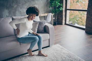 Photo of pretty dark skin curly lady sitting sofa holding hand on spine suffering from strong back ache pms period wear casual sweater jeans outfit flat indoors