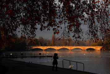 A woman walks beside the Serpentine lake in the early morning in Hyde Park, London