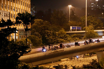 Protesters who leave Hong Kong Polytechnic University by abseiling down from a bridge onto a flyover are taken away by motorbikes as riot police officers are seen on the ground, in Hong Kong