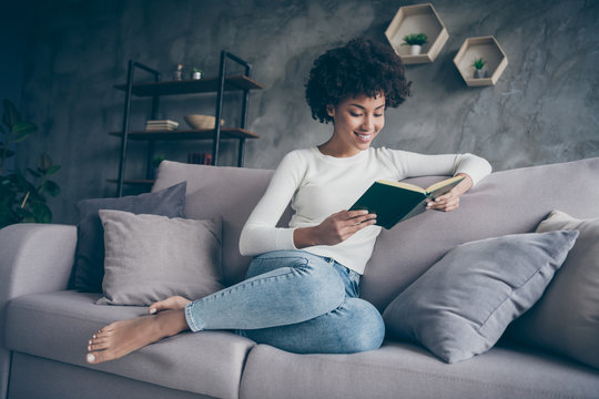 Photo of attractive dark skin curly lady holding favorite historic love novel hands reading excited best moment sitting cozy couch wear casual sweater jeans outfit flat indoors