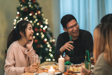 Merry Christmas and Happy New Year! Young friends group having dinner at home. Asian family party with beer and pizza food near christmas tree at house in night. Celebration holiday and togetherness.
