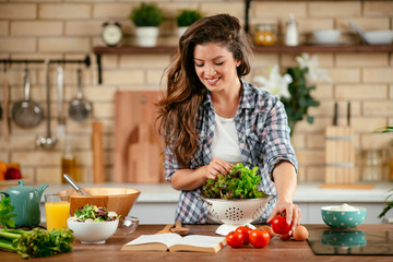 Young woman in kitchen. Beautiful woman making healthy food.