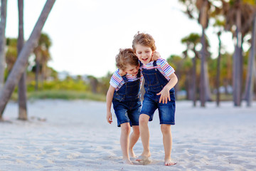 Two little kids boys having fun on tropical beach, happy best friends playing, friendship concept. Siblings brothers, twins fighting, running and jumping in family look with palms trees on background.
