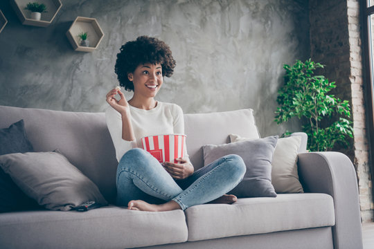 Photo of pretty funny dark skin wavy lady homey mood eating popcorn watching favorite humor television show sitting cozy couch casual sweater jeans outfit flat indoors