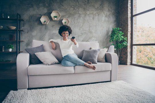 Photo of pretty dark skin wavy lady homey mood holding tv remote control changing channel searching favorite humor show sitting cozy couch casual outfit flat indoors