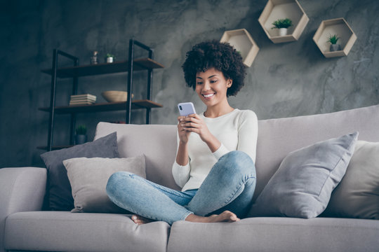 Photo of pretty dark skin wavy lady homey domestic atmosphere texting telephone with friends reading instagram comments sitting cozy couch casual outfit flat loft indoors