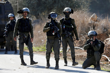 Israeli border policeman aims his weapon during a protest against the demolition of under-construction Palestinian houses by Israeli forces near Hebron in the Israeli-occupied West Bank