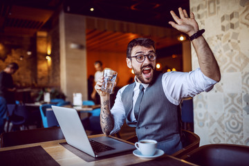 Attractive caucasian bearded businessman in suit and with eyeglasses holding glass of water and waving while sitting in cafe. On table are laptop and cup of coffee.
