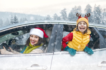 Mother, child and car on snowy winter nature