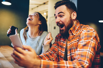 Excited male and female hipsters rejoice in winning an internet lottery made bets on website on modern smartphone.Happy couple in love celebrating victory in online competitions enjoying success