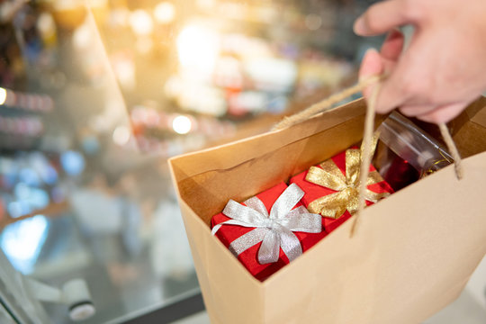Male hand holding paper shopping bag with red gift boxes inside at Christmas event in department store. Buying present for Xmas holiday and New Year celebration concept
