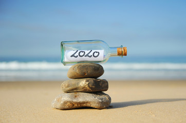 Papiers peints Zen pierres a sable Happy New Year 2020 on the beach. Zen style summer vacation concept. Message in a bottle found on the beach on stones in balance