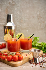 bloody mary cocktail in glasses with straws and lime on wooden board near salt, pepper, tomatoes and celery