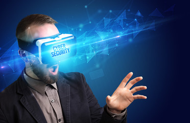 Businessman looking through Virtual Reality glasses with CYBER SECURITY inscription, cyber security concept