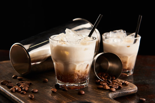 white russian cocktail in glasses with straws on wooden board with coffee grains and shaker isolated on black