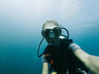 Sportive female taking selfie underwater