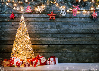 Holidays background with illuminated Christmas tree, gifts and decoration.