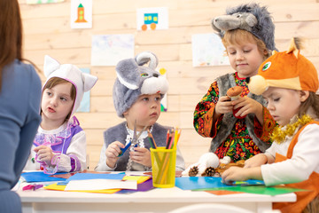 Kids with teacher make hands crafts in kindergarten. Children prepare to christmas holiday. Group of preschoolers on lesson in classroom