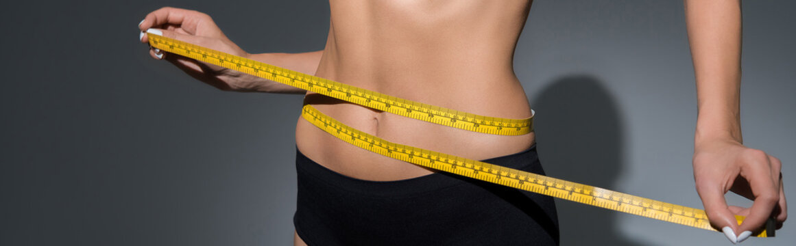 cropped view of slim woman in underwear holding measuring tape on waist on dark background, panoramic shot