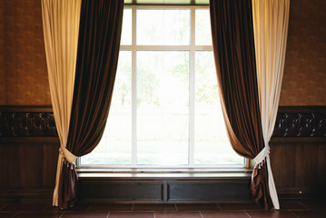 Beige and brown curtains hang on the window, copy space