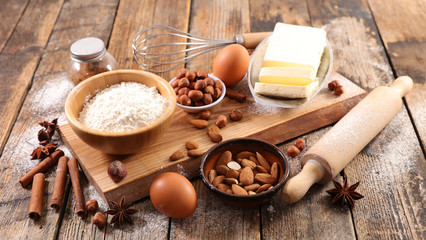 baking food ingredient on wooden board, flour-egg-nut-butter and spices
